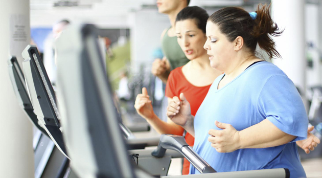 Overweight woman doing cardio workout on a treadmill with her coach assisting.She's doing light jogging and wearing blue t-shirt.Her coach is strongly supporting her wearing red tank top.There are several people in background exercising,out of focus.This woman is dedicated to her goal which is 50 pounds in 6 months without starvation. No junk food though.