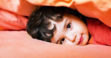Bambino che sorride sotto il cuscino