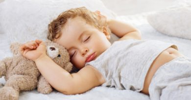 Portrait of a sleeping baby boy 11 months old lying down arms raised up, on a white fur blanket with a Teddy bear touching his forehead, his grey top raised up showing his navel, France