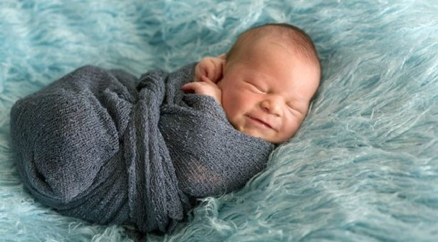 0_Happy-smiling-newborn-baby-in-wrap-sleeping-happily-in-cozy-blue-fur-cute-infant-baby