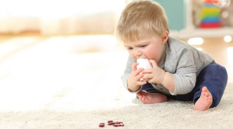 Baby in danger playing with a bottle of medicines on the floor at home