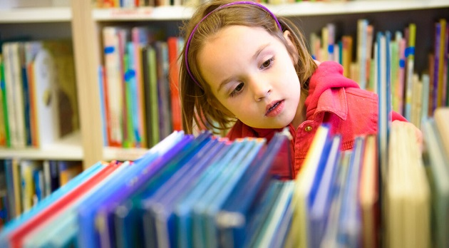 Little Girl Is Choosing A Book In The Library